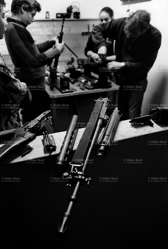 "Switzerland. Canton Ticino. Porte Valentino. Outdoor shooting range. Tiro delle castagne (chestnut shooting) organized by the Società Tiratori del Lucomagno. A group of young men and a woman clean their  weapons, each a  Fass 90. The people are all members of a swiss riflemen's association. The SG 550 is an assault rifle manufactured by Swiss Arms AG (formerly Schweizerische Industrie Gesellschaft) of Neuhausen, Switzerland. ""SG"" is an abbreviation for Sturmgewehr, or ""assault rifle"". The rifle is based on the earlier 5.56mm SG 540 and is also known as the Fass 90 or Stgw 90. An assault rifle is a selective-fire rifle that uses an intermediate cartridge and a detachable magazine. A shooting range or firing range or pistol range or rifle range or shooting gallery or shooting ground is a specialized facility designed for firearms practice. Ponto Valentino is a village and is part of  the municipality Acquarossa in the canton of Ticino. 4.11.2017 © 2017 Didier Ruef"