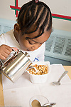 Education Childcare 3 year olds breakfast girl pouring own milk into cereal container