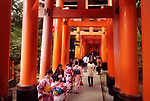 Tourists and women in kimono walking along a long Torii path, Senbon torii, a row of orange gates, at Fushimi Inari Taisha head shrine in Fushimi Ward, Kyoto, Japan 2017