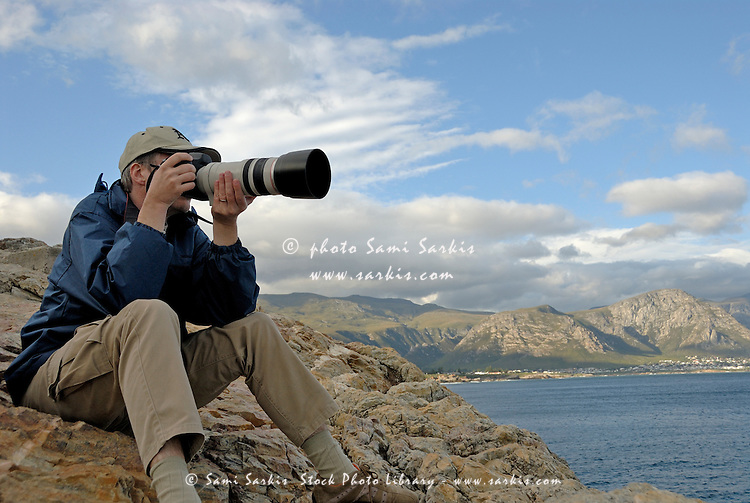 Man taking photograph of a landscape with telephoto, Hermanus, South Western Cape, South Africa