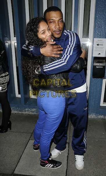 "guest & Ashley Walters.The ""Streets : A New Kind of Musical"" VIP night, The Cockpit Theatre, London, England..April 9th, 2013.full length blue trousers leather jacket black white stripe hug embrace tracksuit .CAP/CAN.©Can Nguyen/Capital Pictures."