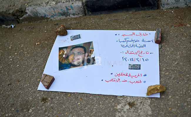 A pictures and placard is seen laid on a street in a show held by students against the arrest of the students of Universities, and against the military rule, outside Cairo University on November 05, 2014. Photo by Amr Sayed