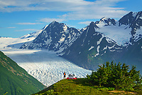 Man stands by tent camp in the mountains overlooking Spencer Glacier in the Chugach National Forest, Kenai Peninsula, Alaska.