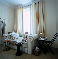 An upholstered daybed sits beneath the window in the dressing room