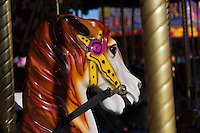 A sunlit closeup of one of the painted horses at the Orange County Fairgrounds carousel (merry-go-round).