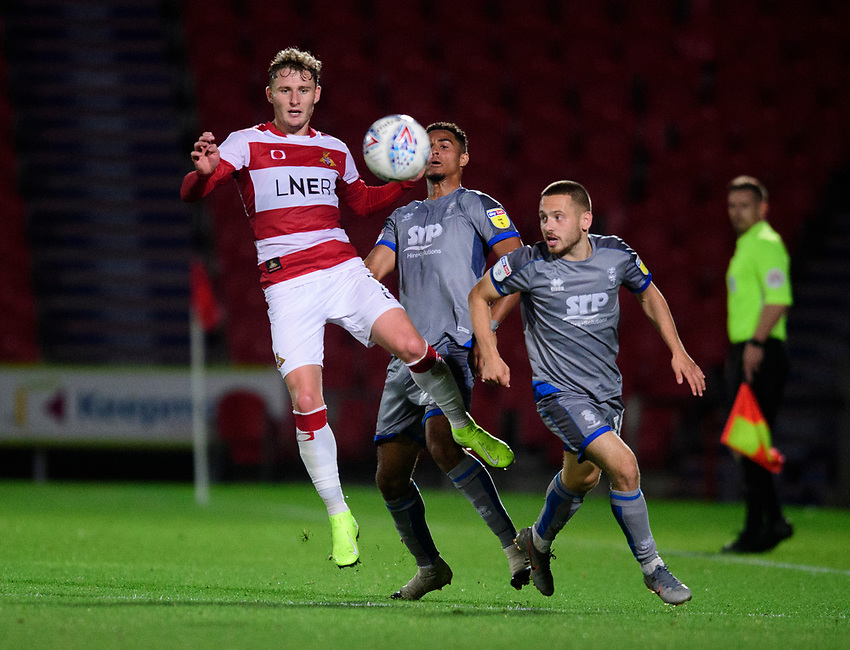 Lincoln City's Max Melbourne, centre, and Lincoln City's Jack Payne vie for possession with Doncaster Rovers' Kieran Sadlier<br /> <br /> Photographer Chris Vaughan/CameraSport<br /> <br /> EFL Leasing.com Trophy - Northern Section - Group H - Doncaster Rovers v Lincoln City - Tuesday 3rd September 2019 - Keepmoat Stadium - Doncaster<br />  <br /> World Copyright © 2018 CameraSport. All rights reserved. 43 Linden Ave. Countesthorpe. Leicester. England. LE8 5PG - Tel: +44 (0) 116 277 4147 - admin@camerasport.com - www.camerasport.com
