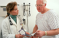 Physician talks with mature man during office consultation.