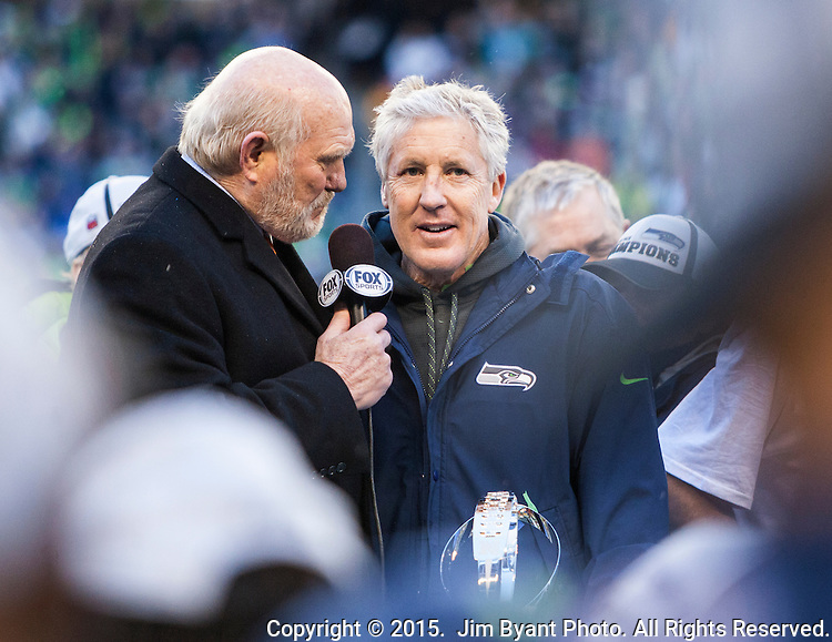 Hall of Fame NFL quarterback, and  FOX sports broadcaster Terry Bradshaw, left, interviews Head Coach Pete Carroll, center,  after their 28-22 overtime in the NFC Championship game against the  Green Bay Packers at CenturyLink Field in Seattle, Washington on January 18, 2015.  The Seattle Seahawks beat the Green Bay Packers in overtime 28-22 for the NFC Championship Seattle.  ©2015. Photo by Jim Bryant, All Rights Reserved.