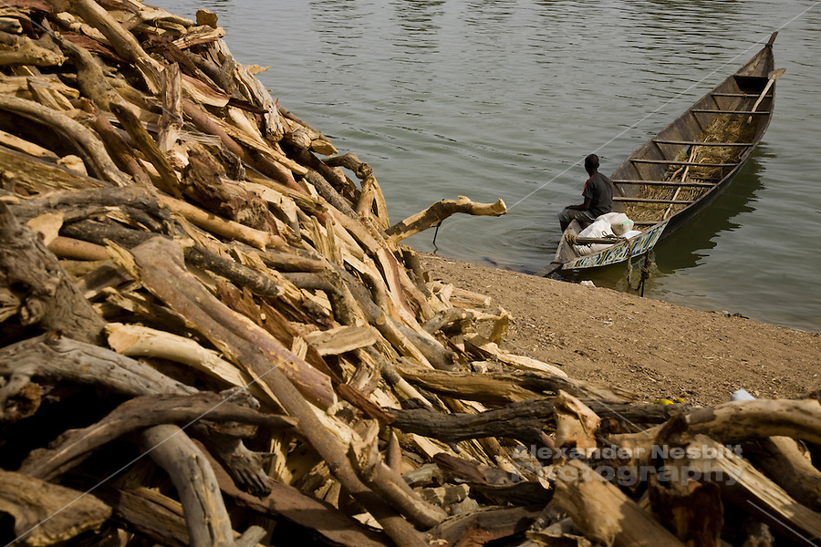 Korioume, Mali 2009 -   A boy rests in a workboat on the Niger River near the port of Korioume. Behind him is a massive load of firewood hauled into this arid region from a more verdant part of Mali.