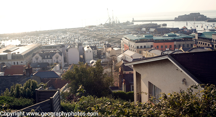 Early morning contre-jour view over St Peter Port town and harbour, Guernsey, Channel Islands, UK