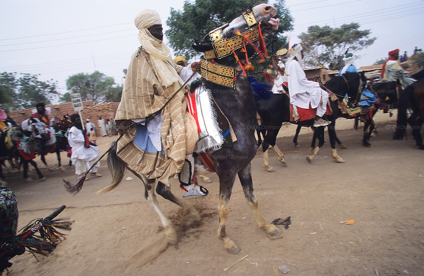 A rider and his horse on the streets of Kano during the Durbar Fantasia..The Durbar Fantasia, is the moment where The Husa residents of Kano wear traditional dress, their local leaders and chiefs mount horses, and together with their militias display allegiance and homage to their leader, the Emir of Kano. This takes place after Ramadan. The Emir is Kano's State official political and economic feudal leader, everyone seeks to be in his pleasure, otherwise they reap the consequences..Kano is the largest Muslim Husa city, under the feudal, political and economic rule of the Emir. Kano and the other eleven northern states are under Islamic Sharia Law which is enforced by official state apparatus including military and police, Islamic schools and education, plus various volunteer Militia groups supported financially and politically by the Emir and other business and political bodies. 70% of the population live below the poverty line. Kano, Kano State, Northern Nigeria, Africa