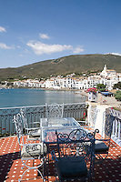 Wrought iron chairs and a glass topped table on a tiled terrace giving a view of Cadaques, famous for its whitewashed facades of village houses
