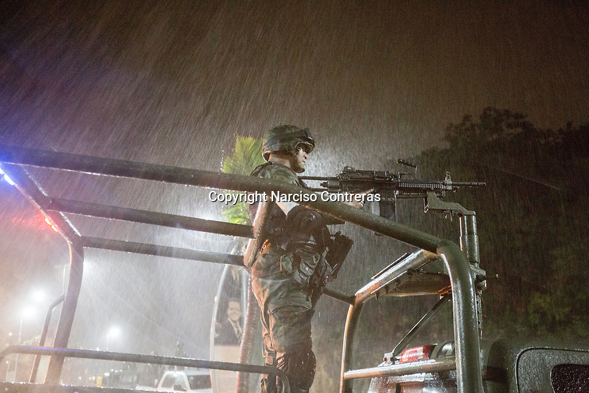 """June 16, 2018: A Mexican army soldier keeps watching as a military convoy surveils """"La Quebrada"""" touristic boulevard during a storm in Acapulco, Guerrero. A juncture of security forces, among them military, marines, federal police and local police joined under one-command to fight crime violence in the once-glamorous resort destination."""
