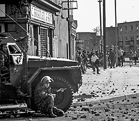British soldier with rifle shelters from stone throwers behind an armoured personnel carrier at the interface with the Bogside area of Londonderry in August 1969. 196908000004...Copyright Image from Larry Doherty, c/o Victor Patterson, 54 Dorchester Park, Belfast, UK, BT9 6RJ..Tel: +44 28 9066 1296.Mob: +44 7802 353836.Voicemail +44 20 8816 7153.Skype: victorpattersonbelfast.Email: victorpatterson@mac.com.Email: victorpatterson@ireland.com (back-up)..IMPORTANT: If you wish to use this image or any other of my images please go to www.victorpatterson.com and click on the Terms & Conditions. Then contact me by email or phone with the reference number(s) of the image(s) concerned.