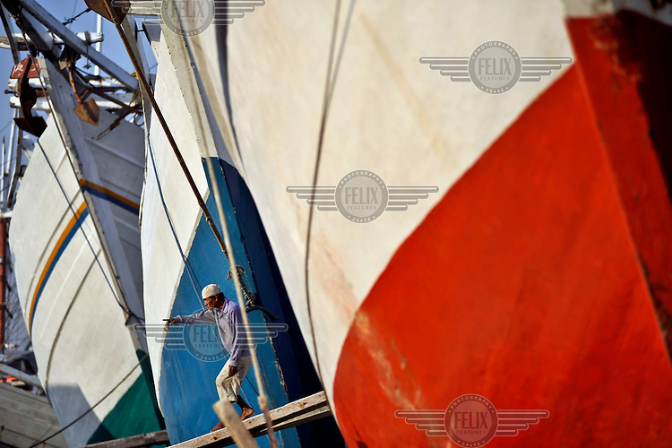 A man points from the gangplank of a traditional 'Prahu' wooden sailing ship, one of many lined up in the Sunda Kelapa port. These vessels are a vital link in disbursing consumer goods from Java throughout the 17,000 islands that make up the Indonesian Archipelago.