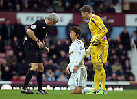 Sunday 07 December 2014<br /> Pictured L-R: Match referee Chris Foy sees to injured Ki Sung Yueng of Swansea and Adrian goalkeeper for West Ham<br /> Re: Premier League West Ham United v Swansea City FC at Boleyn Ground, London, UK.
