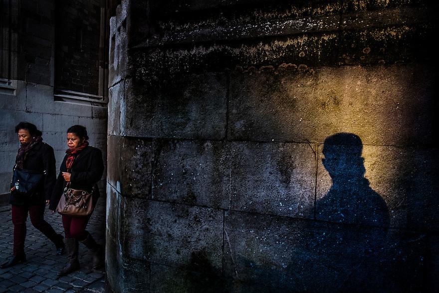 Nederland, Utrecht, 23 feb 2014<br /> Schaduw op een muur in een lichtvlek van de zon en twee vrouwen die uit een steegje komen. Lijkt een bedreigende situatie. <br /> <br /> Foto(c): Michiel Wijnbergh