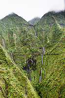 Waterfalls on the side of a green cliff on Kaua'i