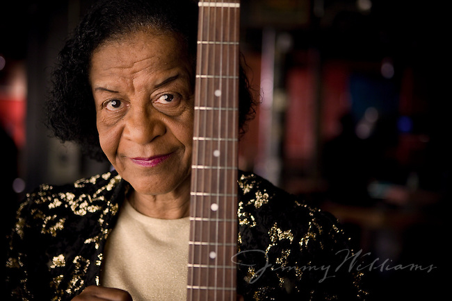 An elderly african-american woman poses with her electric guitar in a dimly lit bar.