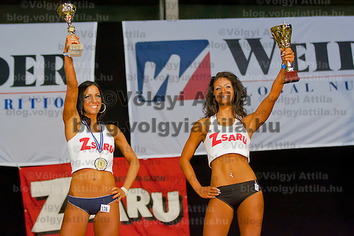 Competitors Zsofia Horvath (L) winner of the over 165 cm category and Rita Kovari (R) winner of the under 165 cm category celebrates her victory during the Miss Zsaru (Miss Cop) contest in Budapest, Hungary on May 13, 2012. ATTILA VOLGYI