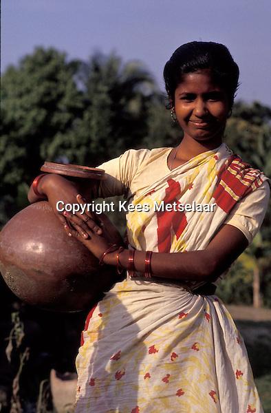 Bangladesh, Chittagong, 26 Januari 1991..Jonge vrouw in mooie jurk met aardewerken pot...Young woman in nice dress with clay pot...Photo by Kees Metselaar
