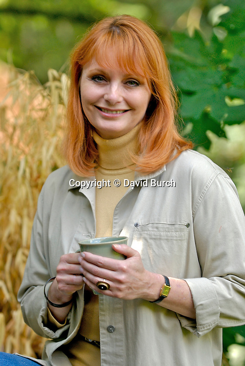 Mature woman smiling holding tea cup, portrait