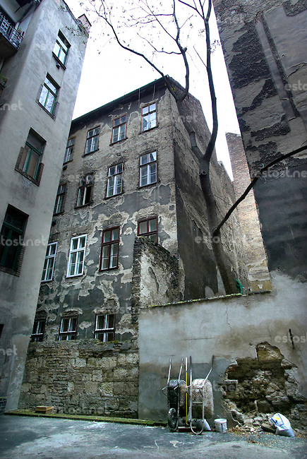 "UNGARN, 04.2009.Budapest - VII. Bezirk .Reste der Ghettomauer (Judenvernichtung 1944/45) im  alten Juedischen Viertel der Elisabethstadt (Erzs?betv?ros):  Die L-f?rmige Mauer auf den Hoefen der Sip utca 7 (links) und 5 (rechts) versperrte den Ausweg zur Dohany utca 26 (Mitte). Die Ghettogrenze verlief in Budapest nicht entlang von Strassen, sondern wurde hinter den Haeusern ueber Brandwaende und entsprechend verstaerkte Hofmauern gefuehrt, was Aufwand und Sichtbarkeit minimierte..Remains of the Ghetto wall (Holocaust 1944/45) in the old Jewish quarter of the ""Elizabethtown"" district: The L-shaped wall in the courtyards of Sip street 7 (left) and 5 (right) cut off the exit to Dohany street 26 (middle). The ghetto boundary in Budapest did not follow open streets, but was drawn behind the houses using party walls and reinforced courtyard walls, thus minimizing effort and visibility..© Martin Fej?r/EST&OST"