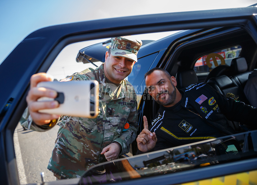 Nov 10, 2017; Pomona, CA, USA; NHRA top fuel driver Tony Schumacher (right) takes a selfie photo with a US Army soldier on Veterans Day during qualifying for the Auto Club Finals at Auto Club Raceway at Pomona. Mandatory Credit: Mark J. Rebilas-USA TODAY Sports