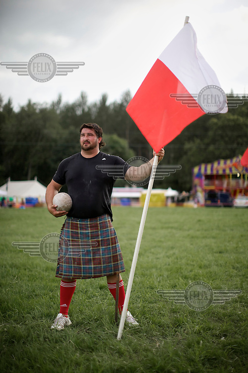 Sebastian Wenta is a Polish shot put champion, three time winner of the World Highland championship and was second in the World's Strongest Man 2007. Here he stands holding the Polish flag at the Callander Highland Games, Stirlingshire.