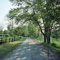 The dirt access road to the property is framed by handmade wooden fences by garden designer Nancy McCabe