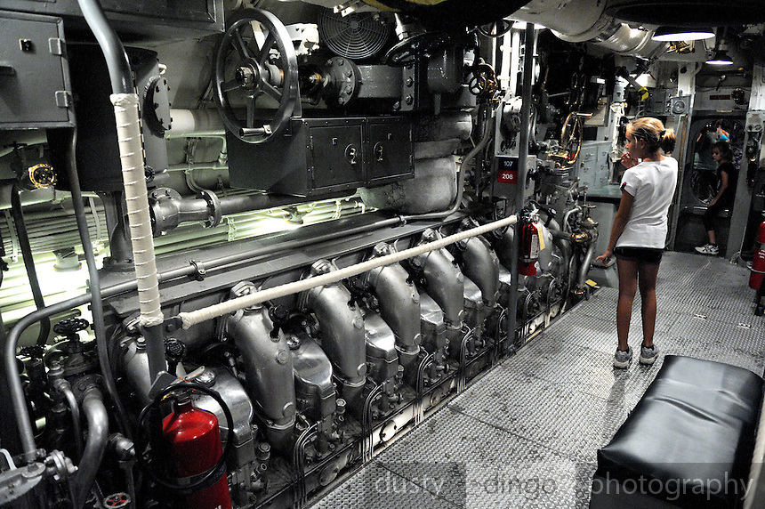 11 year old child standing in engine room of WW2 submarine, the USS Bowfin. USS Bowfin Submarine Museum and Park, part of the USS Arizona Memorial Museum in Pearl Harbour, Hawai.