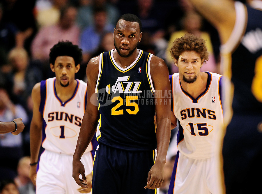 Oct. 12, 2010; Phoenix, AZ, USA; Utah Jazz center (25) Al Jefferson is flanked by Phoenix Suns guard (1) Josh Childress and center (15) Robin Lopez during a preseason game at the US Airways Center. Mandatory Credit: Mark J. Rebilas-