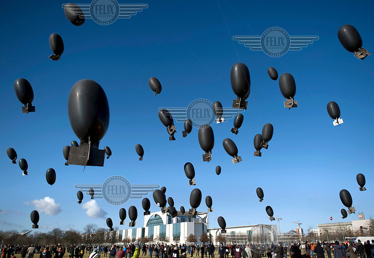 A peaceful protest against the export of weapons with balloons as symbols for bombs in front of the Reichstag and the Chancellory Office in Berlin.