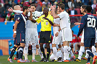 referee Koman Coulibaly is surrounded by players from both USA and Slovenia who disagree with a decision (USA's Clint Dempsey (left))