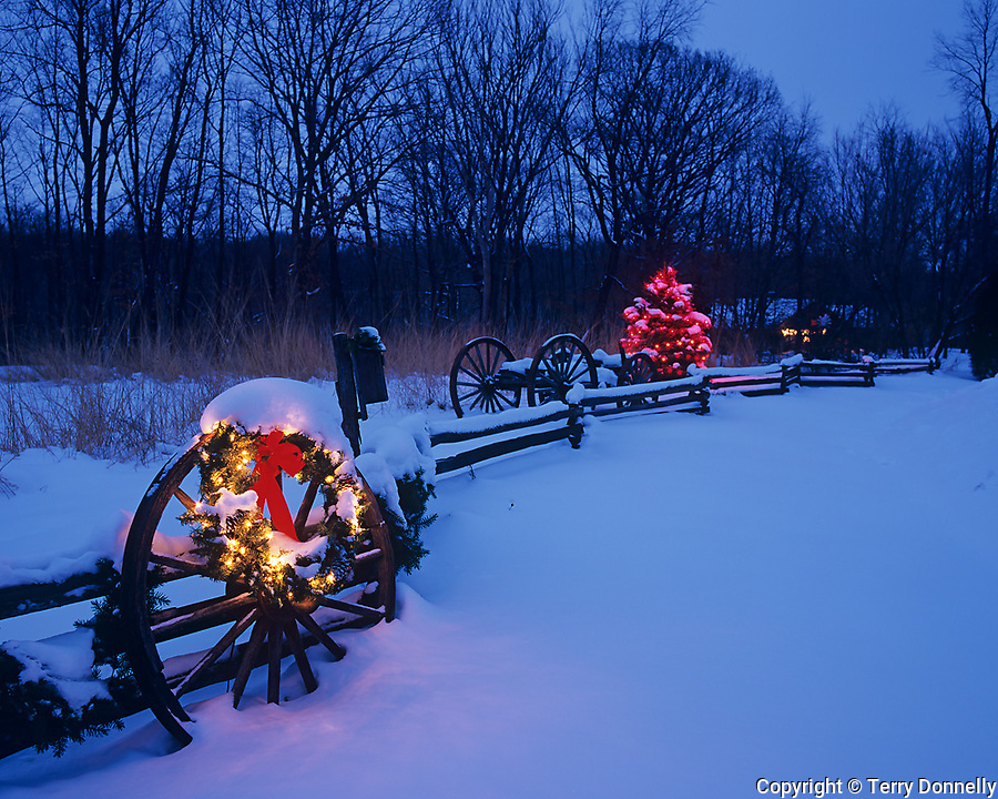 Bureau County, IL <br /> Holiday lights at dusk with fresh snow on a wagon wheel and split rail fence, winter forest in the background.