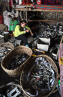 A worker uses a lighter to check plastic as it is sorted in a junk-yard full of e-waste in Guiyu in Guangdong province.