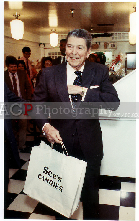 Former U.S. President Ronald Reagan reaches into hit coat pocket as he walks out of a Sees Candy store in Century City, Calif December 8, 1989. Reagan was Christmas Shopping. (Alan Greth)