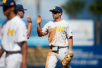 Michigan Wolverines center fielder Jonathan Engelmann (2) high fives teammates in between innings leads off first base during a game against Army West Point on February 18, 2018 at Tradition Field in St. Lucie, Florida.  Michigan defeated Army 7-3.  (Mike Janes/Four Seam Images)