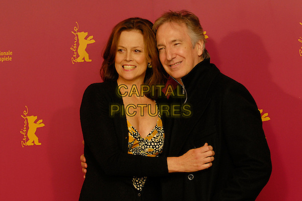 "SIGOURNEY WEAVER & ALAN RICKMAN.Photocall for ""Snow Cake"" at the 56th Berlin (Berlinale) Film Festival, Berlin, Germany..February 9th, 2006.Ref: KRA.half length black coat cardigan smiling.www.capitalpictures.com.sales@capitalpictures.com.©Capital Pictures"