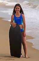 Girl (9-10)  stands with surfboard at beach<br />