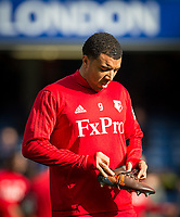 Troy Deeney of Watford checks his boot ahead of the Premier League match between Chelsea and Watford at Stamford Bridge, London, England on 21 October 2017. Photo by Andy Rowland.