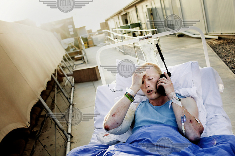 20 year old Danish constable Michael lies on a hospital bed at Camp Bastion speaking on a satelite telephone. He was on foot patrol with his group when a bomb exploded, injuring him and two companions.