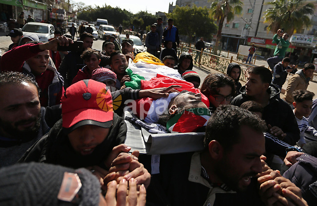 Mourners carry the body of Palestinian, Ehab Abed, 25, who was shot dead by Israeli troops during clashes on Israel-Gaza border, during his funeral in Rafah in the southern of Gaza Strip on January 26, 2019. Photo by Ashraf Amra