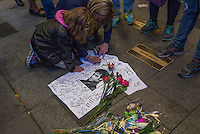 NEW YORK APRIL 21: Two girls signing on aT-shirt at a makeshift memorial place created outside Apollo Theatre in Harlem, New York City, Friday, April 21, 2016. The pop star die a few hours ago at the age of 57.Photo by VIEWpress/Maite H. Mateo