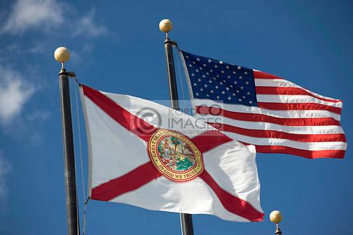 FLORIDA STATE FLAG UNITED STATES FLAG FLYING ON FLAGPOLES ON BLUE SKY BACKGROUND