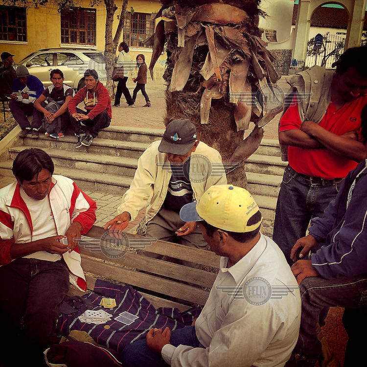 Men play cards and socialise in La Plaza de Tumbaco.