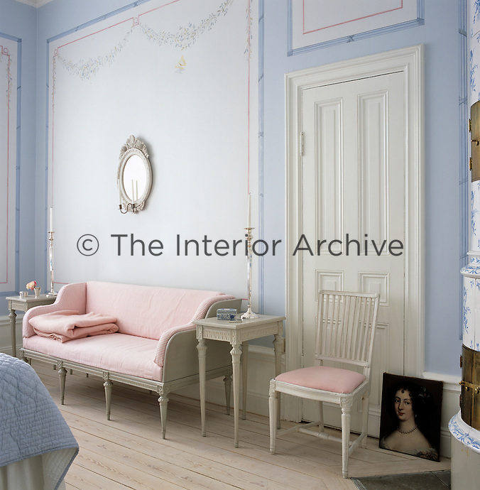 The master bedroom combines blue and pink with expanses of white walls and painted garlands, the sofa is a Solgården reproduction in a narrow striped fabric