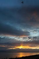 The sun breaks through clouds across the bay as a plane headed to SFO flies over San Francisco Bay.