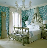 In the master bedroom blue and white floral wallpaper is an effective backdrop for grey-painted antique furniture and a crystal Venetian chandelier