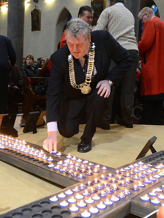 Chairperson of Louth County Council Finnan McCoy places a candle on the cross at the annual SOSAD mass at the Augustinian church Drogheda. Photo:Colin Bell/pressphotos.ie